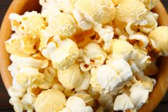 Salted popcorn in a wooden bowl on a wooden table. Salted popcorn in a wooden bowl on a wooden table Stock Image