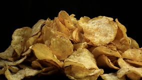 Salted potato chips rotate against black background stock video footage