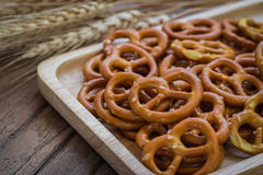 Salted pretzel on wooden plate and wheat Royalty Free Stock Photos