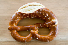 Salted pretzel on wooden table top. Stock Photos