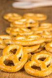 Salted pretzels scattered on the wooden table Royalty Free Stock Images