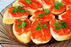 Salted red pieces of salmon on a bread Stock Images