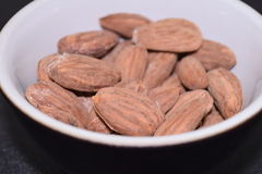 Salted and roasted almonds. Salted and roasted almonds on a black background Stock Images