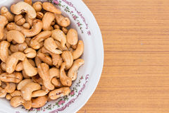 Salted and roasted peanuts in white bowl on wooden table Stock Photos