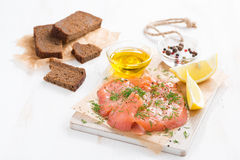 Salted salmon, bread and ingredients on a wooden board Royalty Free Stock Images