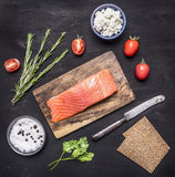 Salted salmon on a cutting board with rosemary, bread for sandwiches, cheese curd and herbs wooden rustic background top view c Stock Image
