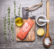 Salted salmon  fillet on a cutting board with rosemary, pepper, oil, lemon and a wooden spoon salt on wooden rustic backgroun Stock Photos