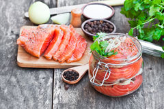 Salted  salmon in glass jar on  an old wooden table Royalty Free Stock Image