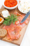 Salted salmon, red caviar, toast and butter, vertical, top view Royalty Free Stock Photography