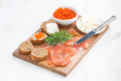 Salted salmon, red caviar, toast and butter on a wooden board Royalty Free Stock Photography