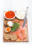 Salted salmon, red caviar, toast and butter on a wooden board Stock Photo