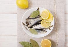 Salted sprat with spice and lemon on the white plate.Wooden tabl. E with coarse tablecloth Stock Images