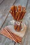 Salted sticks in a glass and on wooden table, with a selective f Royalty Free Stock Photos