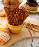 Salted sticks in yellow cup on wooden Royalty Free Stock Image