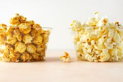 Salted and sweet popcorn in two transparent buckets on pastel colored background, closeup view