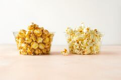Salted and sweet popcorn in two transparent buckets on pastel colored background