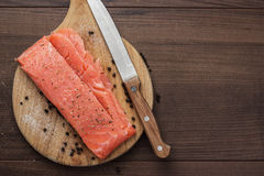Salted trout on the hardboard. And knife Stock Images