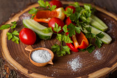 Salter. Handcarved round wooden salter and vegetables on wooden background Stock Images