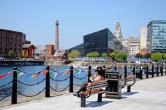 Salthouse Dock, Liverpool. Woman sitting on a bench using her smart phone with views across Salthouse Dock towards the Liver Building and The Pumphouse Stock Photos