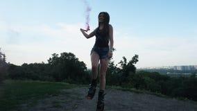 Salti freschi negli stivali di salti di angoo Una donna tiene un controllore con fumo rosso nelle suoi mani e balli contro i prec archivi video
