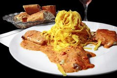 Saltimbocca alla Romana. Stuffed veal scaloppini (with Parma ham & cheese) covered with creamy tomato sauce with herbs. Served with tagliatelle (ribbon) pasta Stock Photo