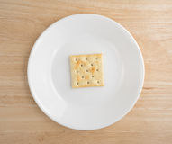 Saltine cracker on a plate atop wood table Stock Photography