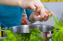 Salting water. Woman is salting boiling water Stock Photo