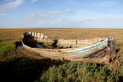 Saltmarsh whaler. An old wrecked whaler lies in the saltmarshes of East Anglia, England amongst a bleak and empty landscape Stock Image