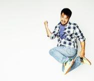 Salto abbastanza asiatico dell'uomo dei giovani allegro contro fondo bianco Fotografia Stock