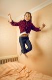 Salto adolescente alegre arriba en su cama Imagen de archivo libre de regalías