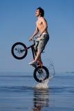 Salto adolescente con la bici en agua Foto de archivo libre de regalías
