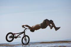 Salto adolescente con la bici en agua Fotografía de archivo