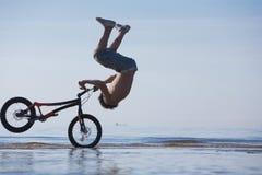 Salto adolescente con la bici en agua Foto de archivo