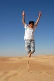 Salto adolescente en el desierto Fotos de archivo