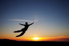 Salto adolescente en la puesta del sol para la diversión Fotografía de archivo