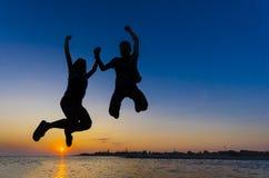 Salto adolescente en la puesta del sol sobre horizonte de mar Fotografía de archivo libre de regalías