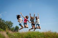 Salto adolescente feliz hermoso de cuatro amigos de muchachas Foto de archivo libre de regalías