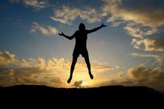 Salto adolescente masculino en puesta del sol Foto de archivo libre de regalías