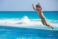 Salto al muchacho emocionado de la piscina Foto de archivo libre de regalías