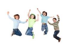 Salto alegre de quatro crianças Foto de Stock Royalty Free