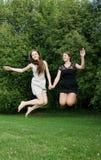 Salto alegre novo de duas mulheres Fotografia de Stock Royalty Free
