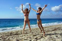 Salto in alto delle giovani donne su una spiaggia Fotografie Stock