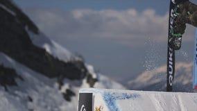 Salto in alto dello Snowboarder dal trampolino Faccia il salto mortale pericoloso Montagne video d archivio