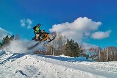 Salto amarillo de la moto de nieve del deporte Día de invierno soleado con el cielo azul Movimiento rápido del concepto Fotos de archivo libres de regalías
