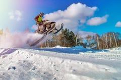Salto amarillo de la moto de nieve del deporte Nube del polvo de la nieve de debajo pistas de la moto de nieve Movimiento rápido  Imagenes de archivo