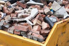 Salto amarillo del contenedor por completo de la basura de la albañilería imagenes de archivo