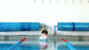 Salto apto de la mujer en piscina almacen de metraje de vídeo