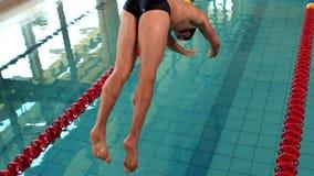 Salto apto del hombre en piscina almacen de metraje de vídeo
