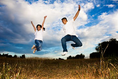salto asiatico di gioia delle coppie fotografie stock