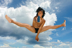 Salto astronómico que hace publicidad del teléfono celular del muchacho tropical asiático. Foto de archivo